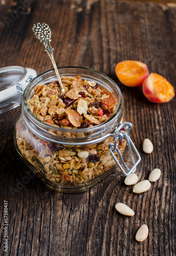 Homemade granola in a glass jar on a vintage board