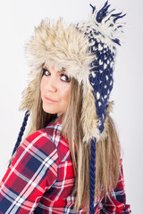 Cute young blonde woman wearing fashionable knitted hat