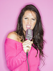 young pretty woman singer with a microphone