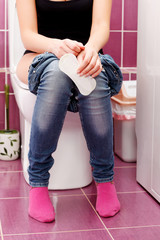 Woman in a toilet with a sanitary napkin