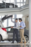 Salesman and customer with brochure looking into hatchback of car in car dealership showroom