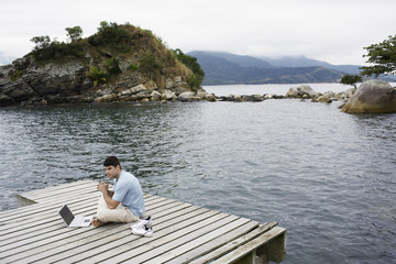 Young man using laptop by lake (high angle view)