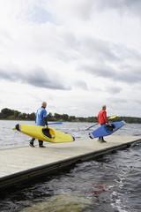 Two senior men carrying kayaks