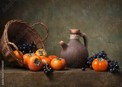 Still life with persimmons and grapes on the table
