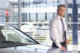 Portrait of confident salesman leaning on car in car dealership showroom