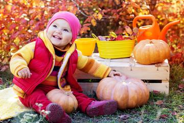 Cute baby girl with pumpkins in autumn garden