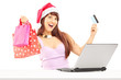 Female holding bags and doing online shopping through laptop