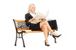 Blond businesswoman sitting on a bench and reading newspaper