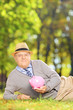Mature gentleman in a park holding a piggy bank