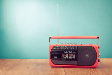 Old retro red radio cassette recorder on table