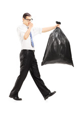 Male closing his nose and carrying a stinky garbage bag
