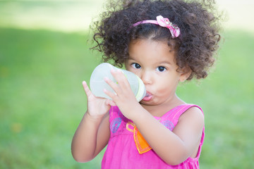 Cute latin girl drinking from a baby bottle