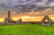Kilmacduagh monastery with stone tower at sunset, Ireland
