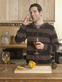 Mid-Adult Man Drinking Wine and Talking on Phone