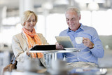 Smiling couple using digital tablets at cafe table