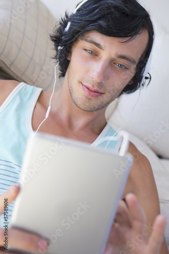 Close up of young man wearing headphones and using digital tablet