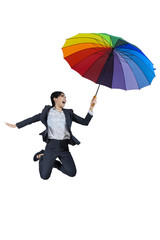 Businesswoman jumping with umbrella