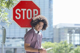 Portrait of smiling young man with headphones using digital tablet against stop sign in city