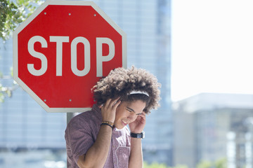 Young man listening to music on headphones against stop sign in city