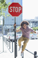 Portrait of enthusiastic young man listening to music on headphones against stop sign in city