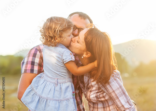 Dad Mom and daughter kissing
