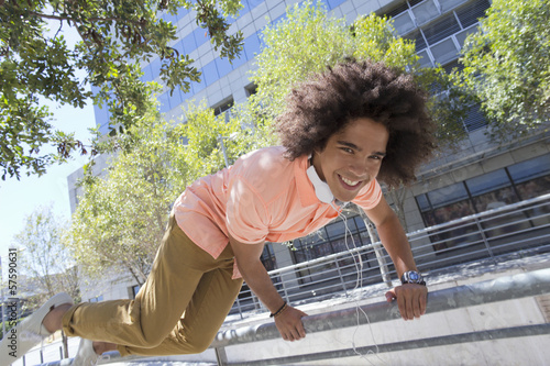 Portrait of smiling young man jumping over railing in city