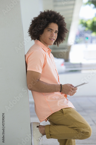 Portrait of smiling young man using digital tablet and leaning against wall