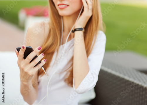 Young beautiful girl listening to mp3 player on the street in a
