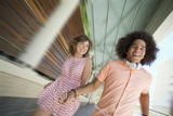 Enthusiastic young couple holding hands and running along corridor