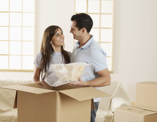 Mid-Adult Couple Unpacking Cardboard Boxes