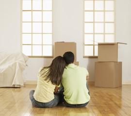 Mid-Adult Couple Sitting on Floor near Cardboard Boxes