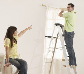 Woman Directing Boyfriend with Curtains