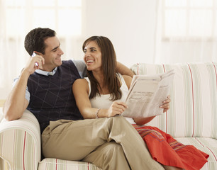 Mid-Adult Couple Reading and Using Mobile Phone on Sofa