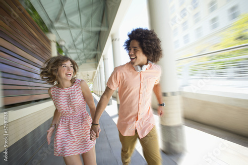 Enthusiastic young couple running along corridor