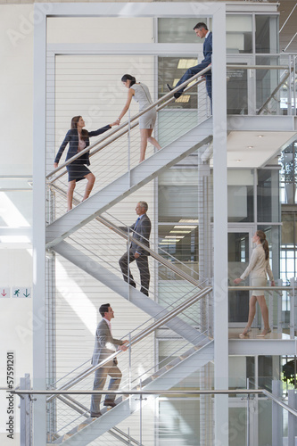 Businessman blocking businesswomen on stairs in office