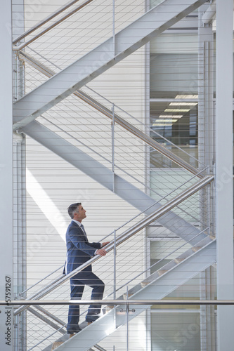 Businessman ascending stairs in office