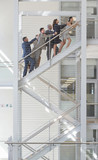 Connected business people ascending stairs in office