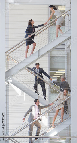 Business people holding hands on stairs in office