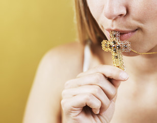 Mid-Adult Woman Kissing Cross