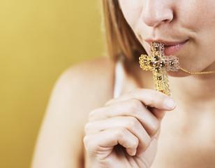 Mid-Adult Woman Kissing Cross