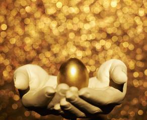Golden Egg on Hand Sculpture