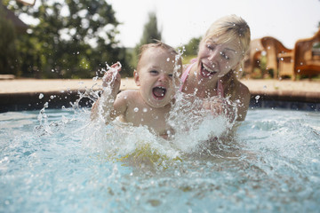 Mother and Baby Boy Splashing in Swimming Pool