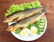 Smoked fish on plate on wooden table