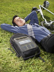 Young Businessman with Bicycle Lying on Grass