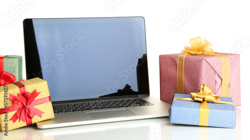 Laptop and gifts isolated on white