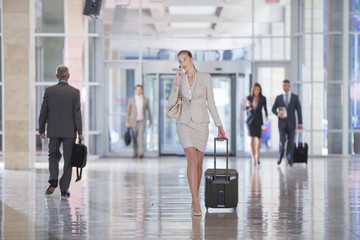 Businesswoman talking on cell phone and pulling suitcase in airport