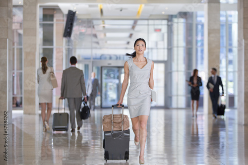 Businesswoman running with suitcase in airport