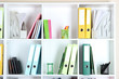 White office shelves with folders and different stationery,