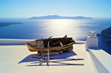 Old wooden boat on the white rooftops of Santorini, Greece