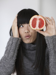 Mid-Adult Woman Eating  Pink Grapefruit